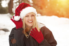 Blonde Girl Wearing Santa Hat and Gloves Outdoors in Snow Royalty Free Stock Images