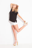 Blonde girl wearing short pants looking up while holding her hee Royalty Free Stock Photography