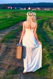 Blonde girl wearing white long dress with retro styled suitcase. On countryside Stock Image