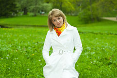 Blonde girl in white on a background of green gras Royalty Free Stock Photos