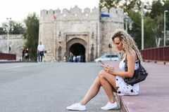 Blonde Girl in a White Dress Sitting on a Sidewalk on the Bridge. Street and Using a Cellphone Stock Image