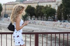 Blonde Girl in a White Dress Standing on the Bridge and Using a. Cellphone Stock Images