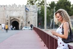 Blonde Girl in a White Dress Standing on the Bridge and Using a. Cellphone Stock Image