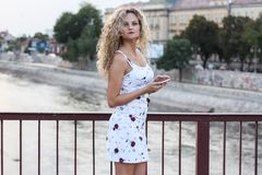 Blonde Girl in a White Dress Standing on the Bridge and Using a. Cellphone Royalty Free Stock Images