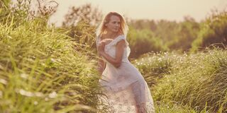A blonde girl in a white dress walks outdoors in the high field grass