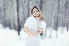 Blonde girl in white dress at winter forest Royalty Free Stock Images