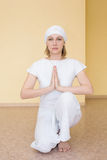 Blonde girl in white practicing yoga in the position Ardha Padmasana royalty free stock photo