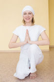 Blonde girl in white practicing yoga in the position Ardha Padmasana Royalty Free Stock Image