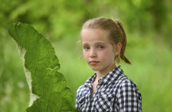 Blonde girl whith a large leaf in her hand Royalty Free Stock Photo