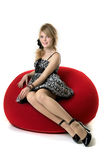 Blonde Girl, Who Sits In A Red Chair Stock Photography