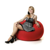 Blonde girl, who sits in a red chair Royalty Free Stock Images
