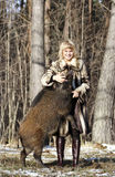 Blonde girl with wild boar. At the forest stock photos