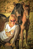 Blonde girl and wild horses Royalty Free Stock Photography