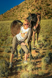 Blonde girl and wild horses Stock Photography