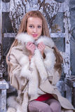 Blonde girl in wooden chair Royalty Free Stock Photos