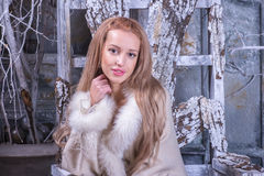 Blonde girl in wooden chair Stock Images