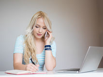 Blonde girl working on laptop Stock Photos