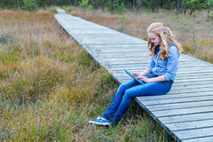 Blonde girl working on tablet computer on wooden path in nature Royalty Free Stock Photography