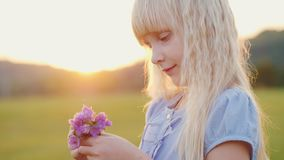 Blonde girl 6 with a bouquet of wildflowers. Standing in the field at sunset, side view. Blonde girl 6 years old with a bouquet of wildflowers. Standing in the stock video footage