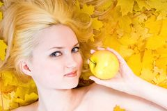 Blonde girl with yellow apple. Over yellow leaves royalty free stock images