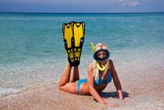 Blonde girl in yellow flippers and swimming mask. Blonde swelte girl in yellow flippers and swimming mask on the sandy sea beach Stock Photo