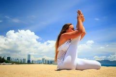 Blonde girl in yoga asana stretched leg on beach Stock Photos