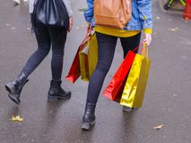 A girl with purchases walking down the street with packages royalty free stock photo