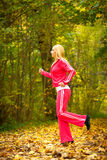 Blonde girl young woman running jogging in autumn  Royalty Free Stock Photo