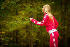Blonde girl young woman running jogging in autumn fall forest park Stock Photos