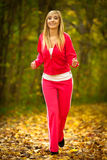 Blonde girl young woman running jogging in autumn fall forest park Stock Photography
