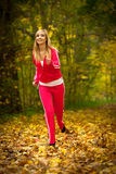 Blonde girl young woman running jogging in autumn fall forest park Royalty Free Stock Photography