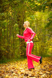 Blonde girl young woman running jogging in autumn fall forest park Stock Image
