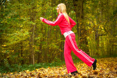 Blonde girl young woman running jogging in autumn fall forest park Stock Photo