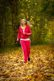 Blonde girl young woman running jogging in autumn fall forest park Royalty Free Stock Photo