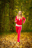 Blonde girl young woman running jogging in autumn fall forest park Royalty Free Stock Images