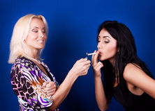 Blonde giving a light to her friend Royalty Free Stock Image
