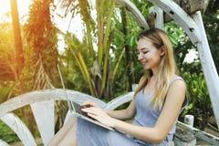 Blonde glückliche Frau benutzt Laptop für Arbeit am sonnigen Tag, Hintergrund von Sonnenscheingrünpalmen in Thailand, Phuket Reis Stockbilder
