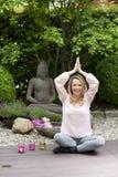 Blonde glückliche Frau betet im Zengarten Lizenzfreie Stockbilder
