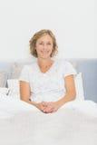 Blonde glückliche Frau, die im Bett lächelt an der Kamera sitzt Stockfoto