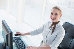 Blonde glückliche Geschäftsfrau, die an Computer arbeitet Stockfotos