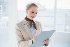 Blonde glückliche Geschäftsfrau, die Klemmbrett hält Lizenzfreie Stockfotografie