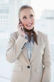 Blonde glückliche Geschäftsfrau, die oben anruft und schaut Stockbilder