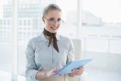 Blonde glückliche Geschäftsfrau, die Tablette hält Lizenzfreie Stockbilder