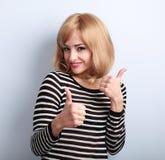 Blonde glückliche junge Frau, die Daumen herauf sugn durch zwei Hände zeigt Lizenzfreies Stockfoto