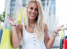 Blonde glückliche junge Frau, die draußen mit Taschen shooping ist Lizenzfreie Stockfotografie