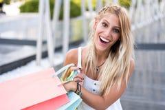 Blonde glückliche junge Frau, die draußen mit Taschen shooping ist Lizenzfreies Stockbild