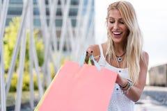 Blonde glückliche junge Frau, die draußen mit Taschen shooping ist Lizenzfreie Stockbilder