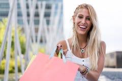 Blonde glückliche junge Frau, die draußen mit Taschen shooping ist Stockbild