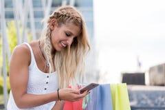 Blonde glückliche junge Frau, die draußen mit Taschen shooping ist Stockfoto