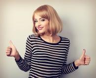Blonde glückliche lächelnde junge Frau, die Daumen herauf Zeichen durch zwei Han zeigt Lizenzfreie Stockfotos
